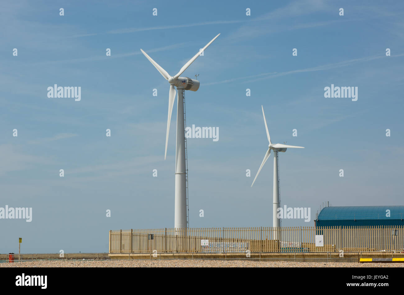 Wind turbine electricity generators on the harbour wall at Shoreham Port, West Sussex, England Stock Photo