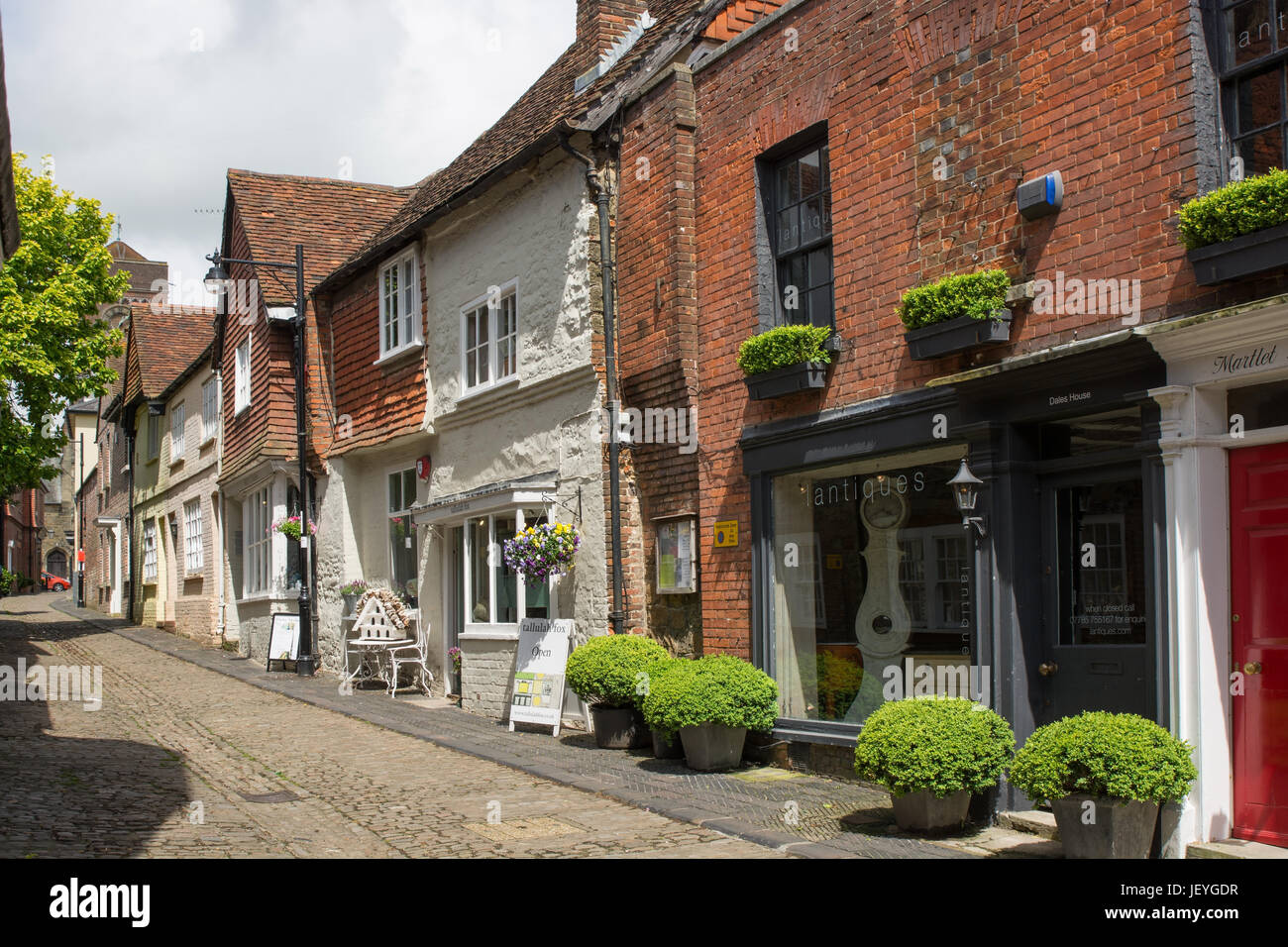 Narrow, cobbled Lombard Street in Petworth, West Sussex, England. With small shops and no people. - Stock Image
