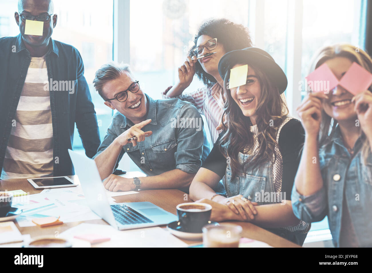 Joking group of diverse young adult coworkers playing with sticky notes on their faces as a distraction during a - Stock Image
