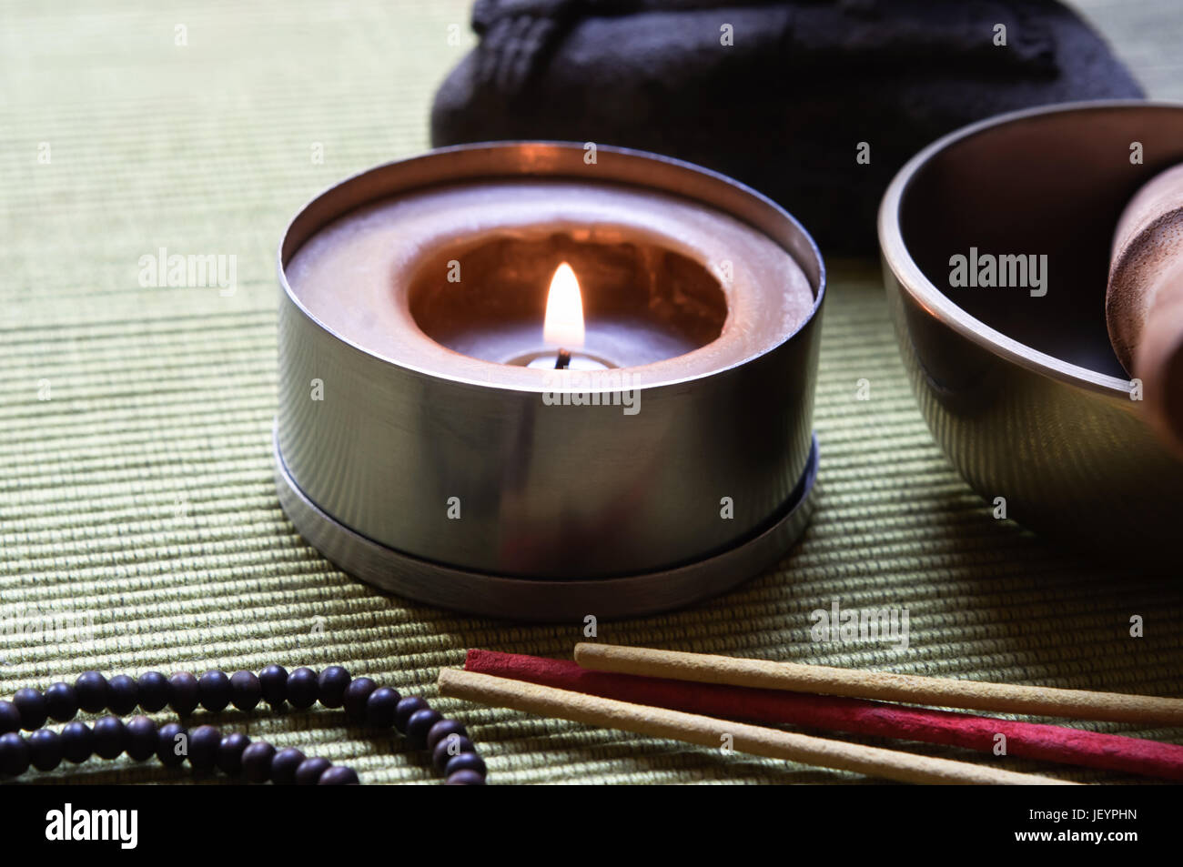 Close up of a collection of Buddhist's objects (candle, josticks, prayer beads and singing bowl), with part - Stock Image