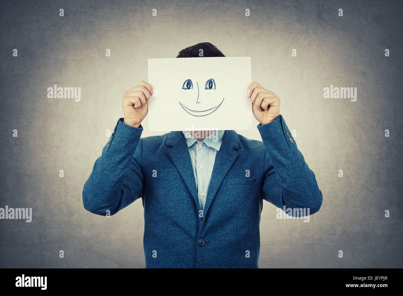 Businessman covering his face using a white paper with drawn smiling emoticon sketch, like a fake mask for hiding - Stock Image
