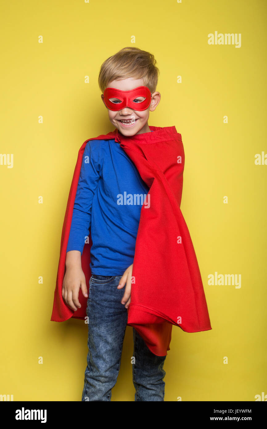 Boy in red super hero cape and mask. Superman. Studio portrait over yellow background - Stock Image