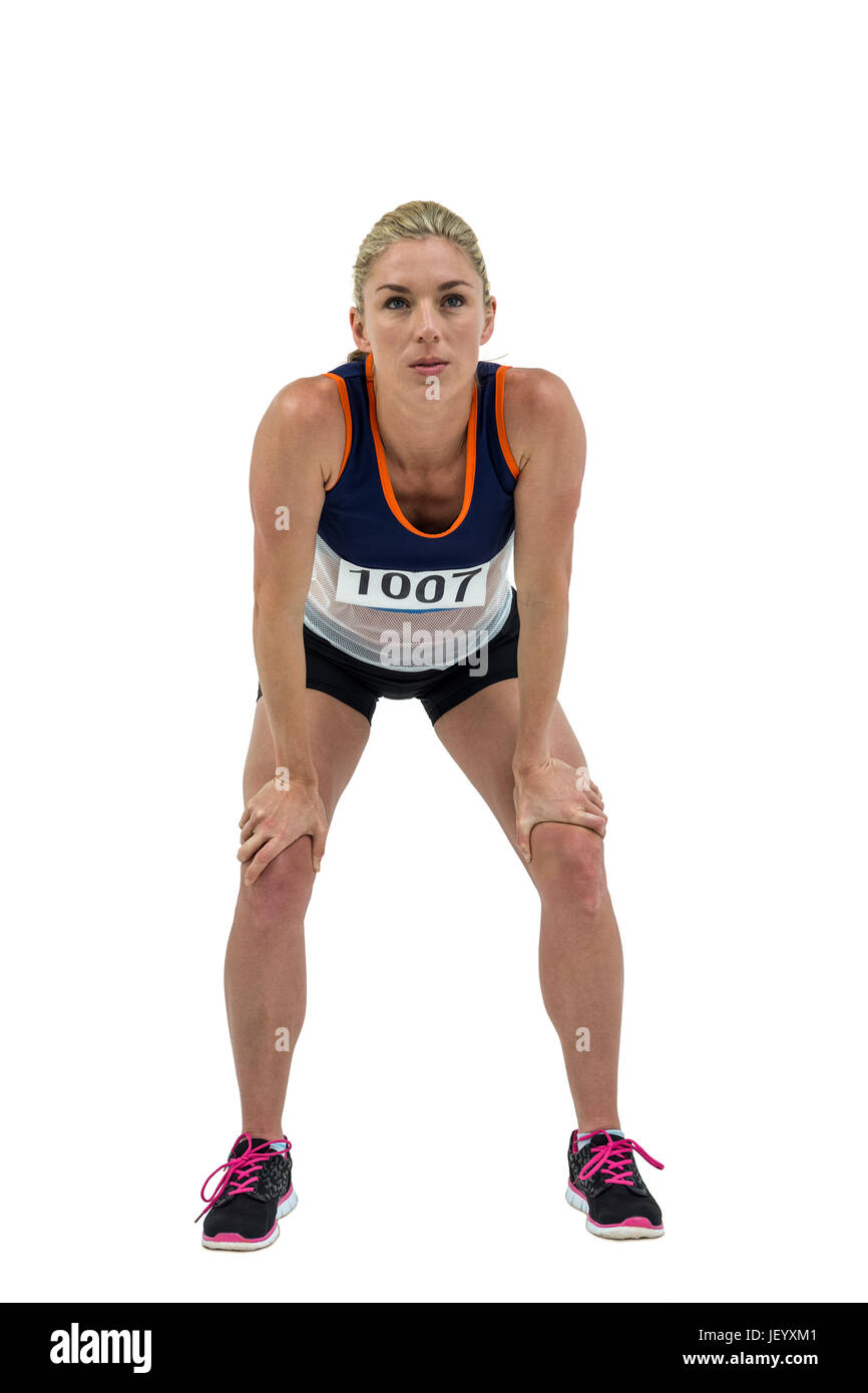 Tired athlete standing with hand on knee Stock Photo