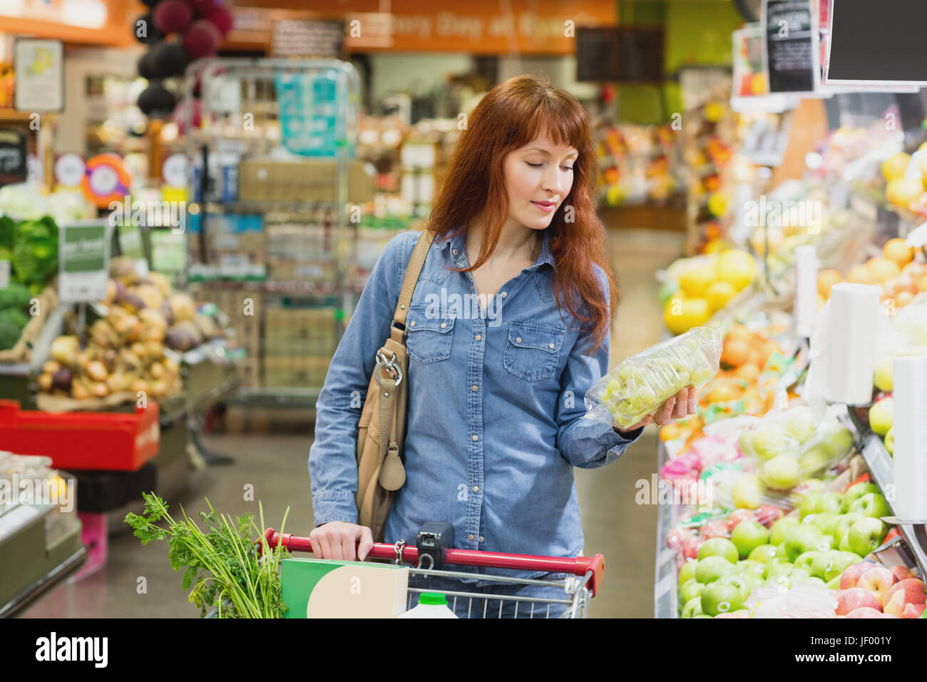 Customer holding a box of grapes - Stock Image