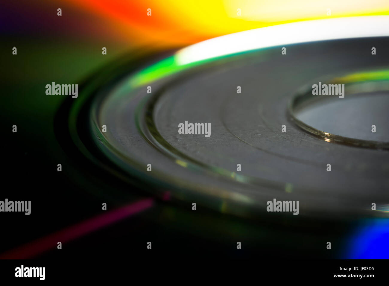 The surface of the CD close-up reflects the spectral colors. - Stock Image