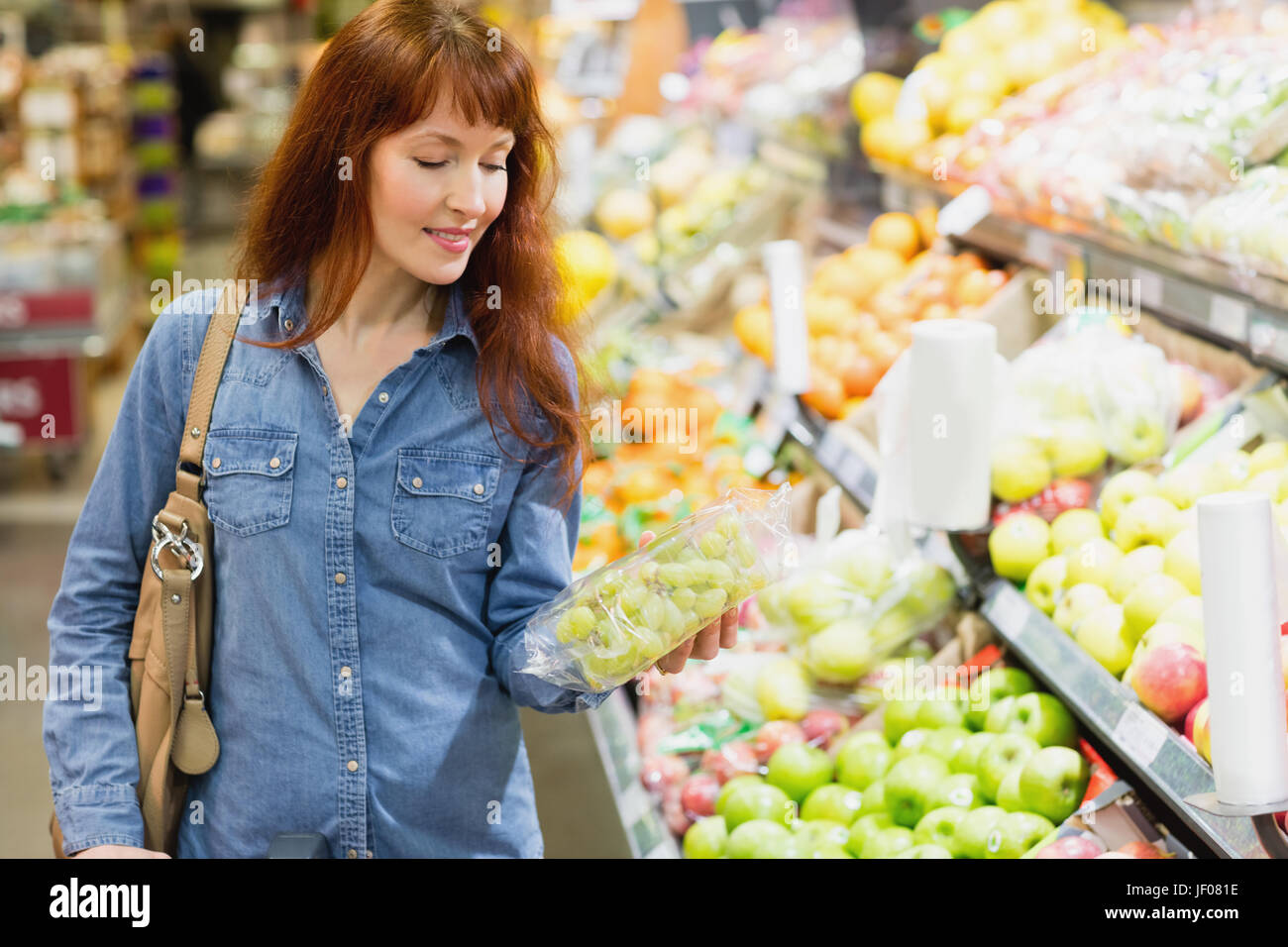Smiling customer holding a box of grapes - Stock Image