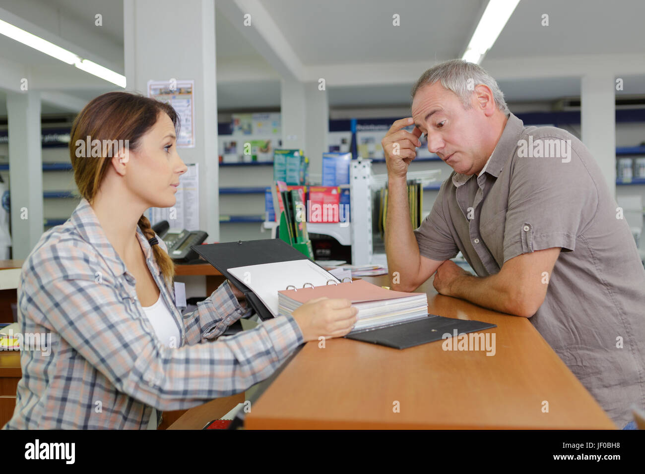 Stressed customer at shop counter - Stock Image