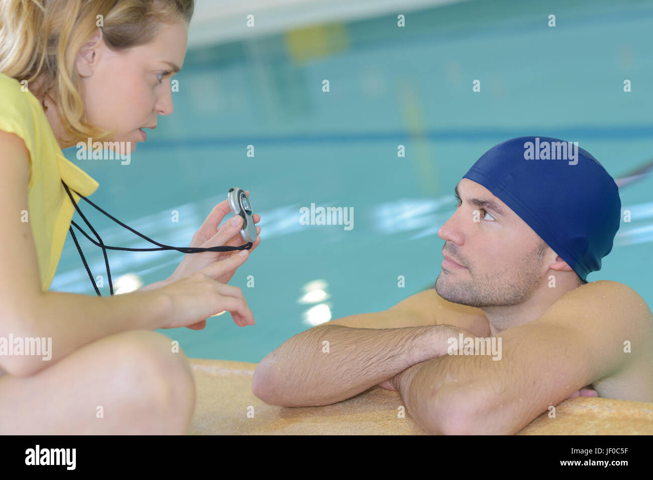 Disappointed coach showing swimmer time on stopwatch - Stock Image