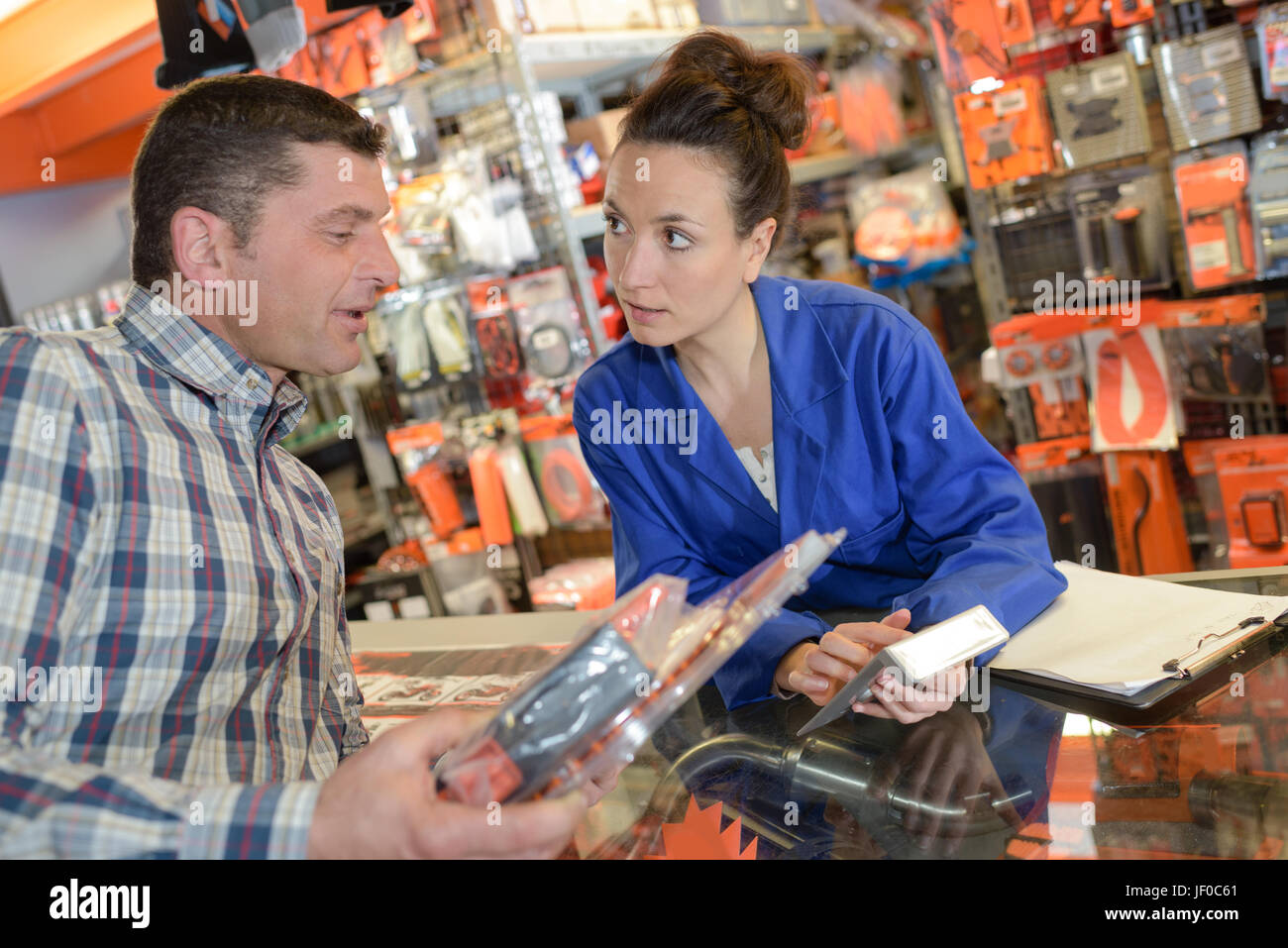 Clerk showing customer the price on a calculator Stock Photo