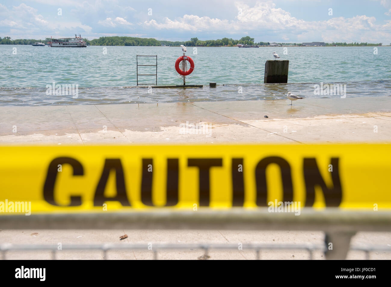 'Caution' yellow tape in front of flooded lakeshore in Toronto - Stock Image