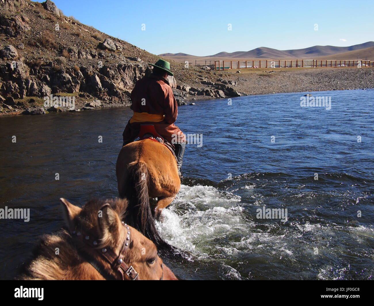Gorkhi Terelj National Park, Mongolia - 01 October, 2016: Mongolian herder crossing a river on horseback - Stock Image
