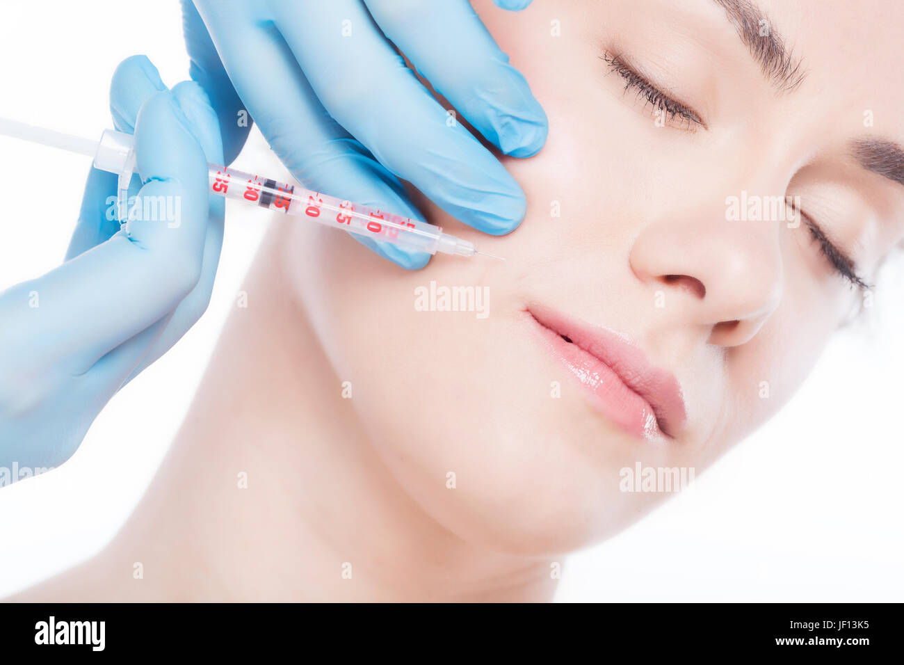 Aesthetic medicine. Young beautiful woman is having botox face injections. Anti-aging skincare and plastic surgery - Stock Image