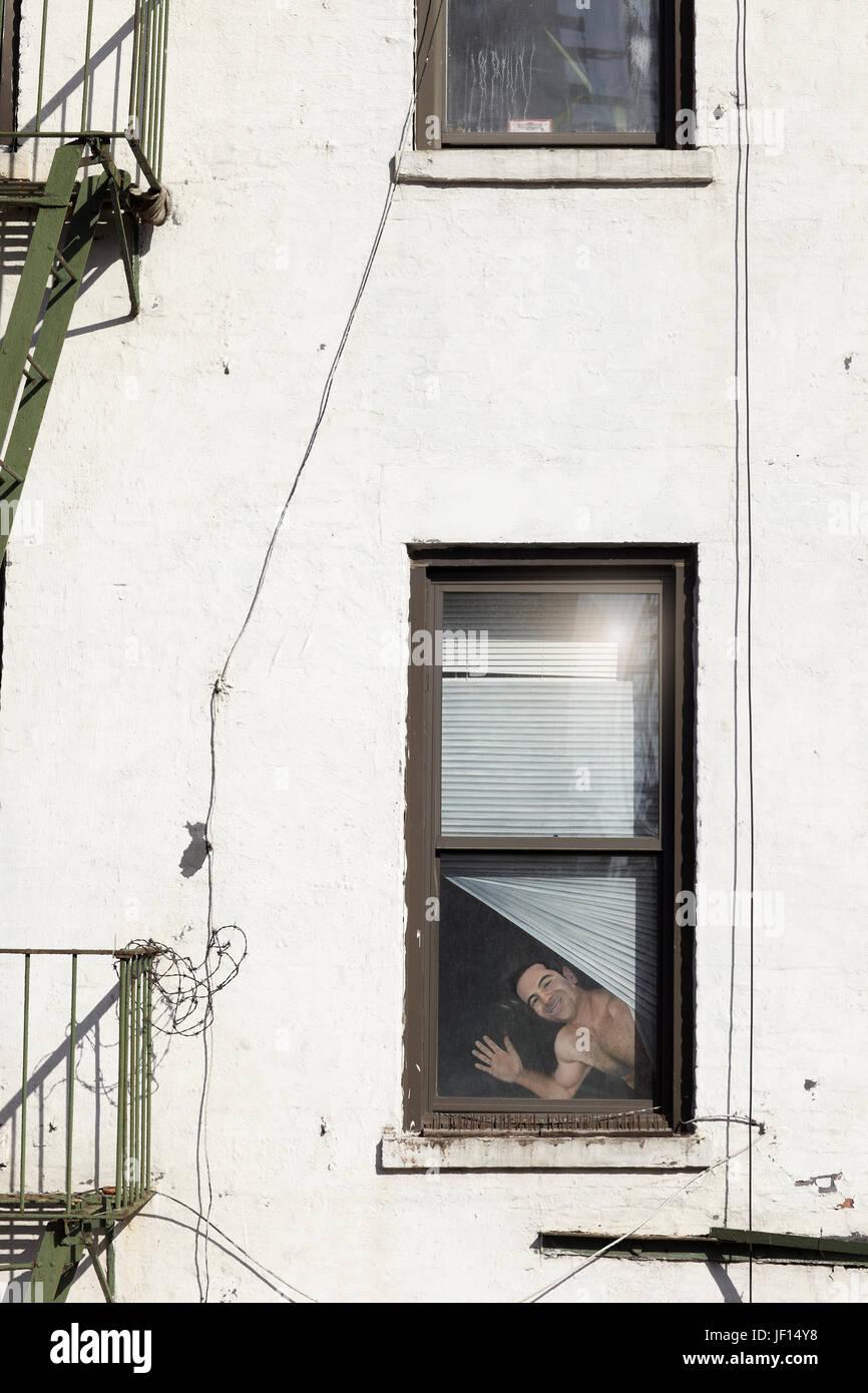 Smiling man looking through window - Stock Image