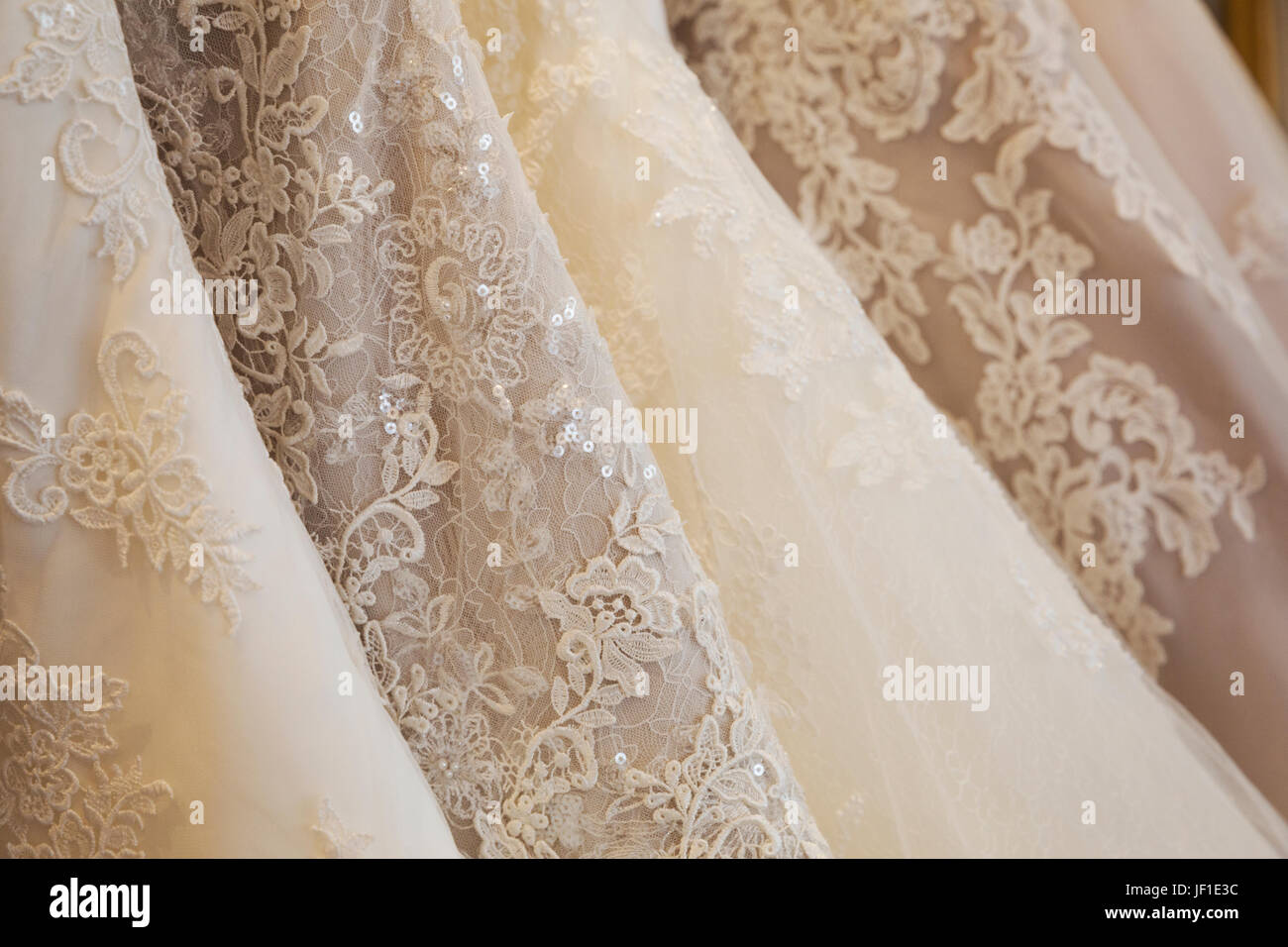 Rows of wedding dresses on display in a specialist wedding dress shop. Close up of full skirts, some with a lace - Stock Image