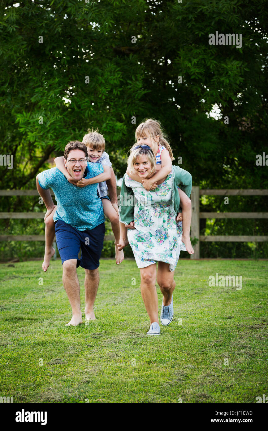 Man and woman running across a lawn, carrying boy and girl piggyback, a family outdoors. - Stock Image