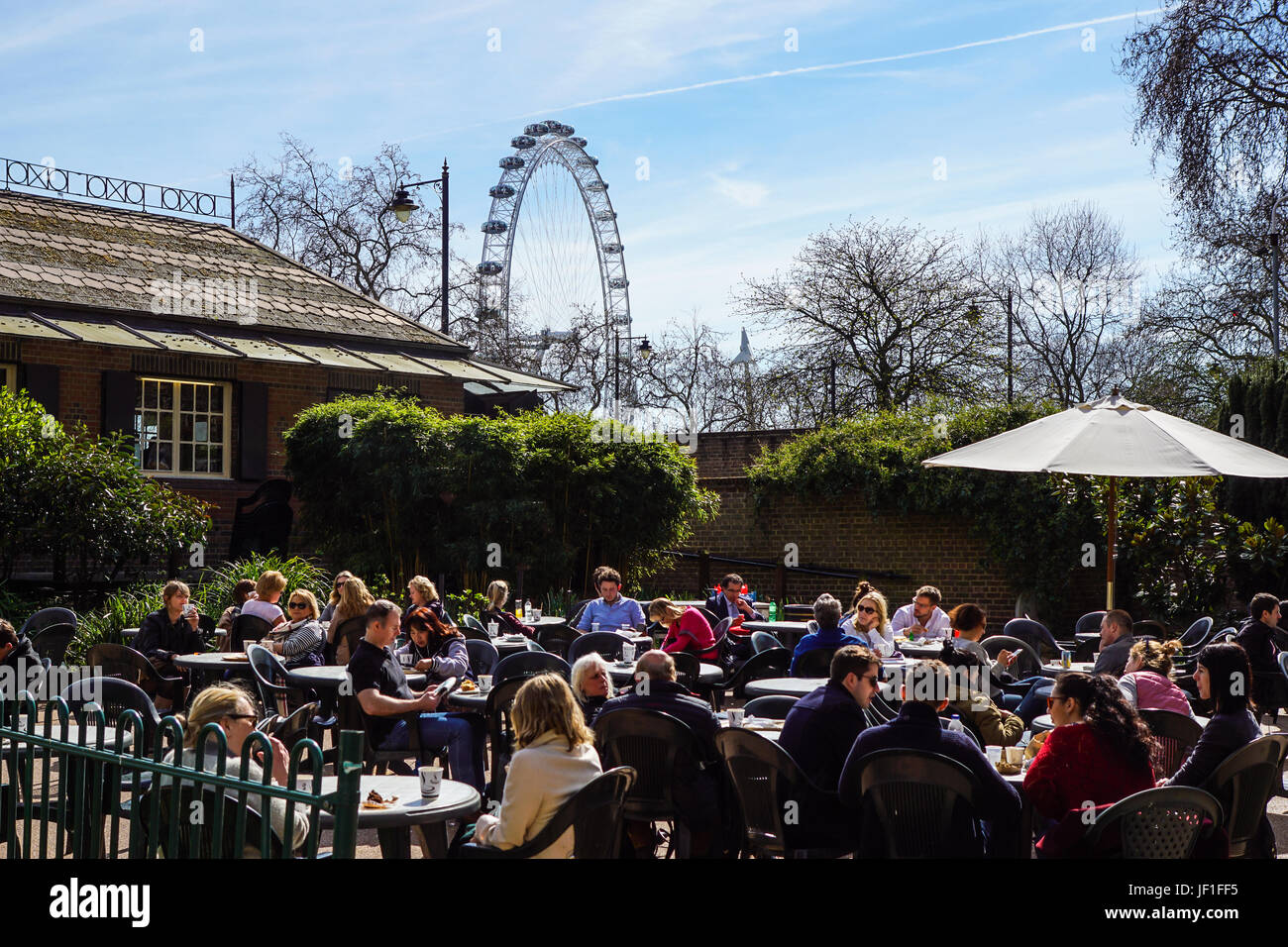 LONDON, ENGLAND, UK - APRIL 24 2017 : unidentified people relax in the park lunch break. Is widespread eating lunch Stock Photo