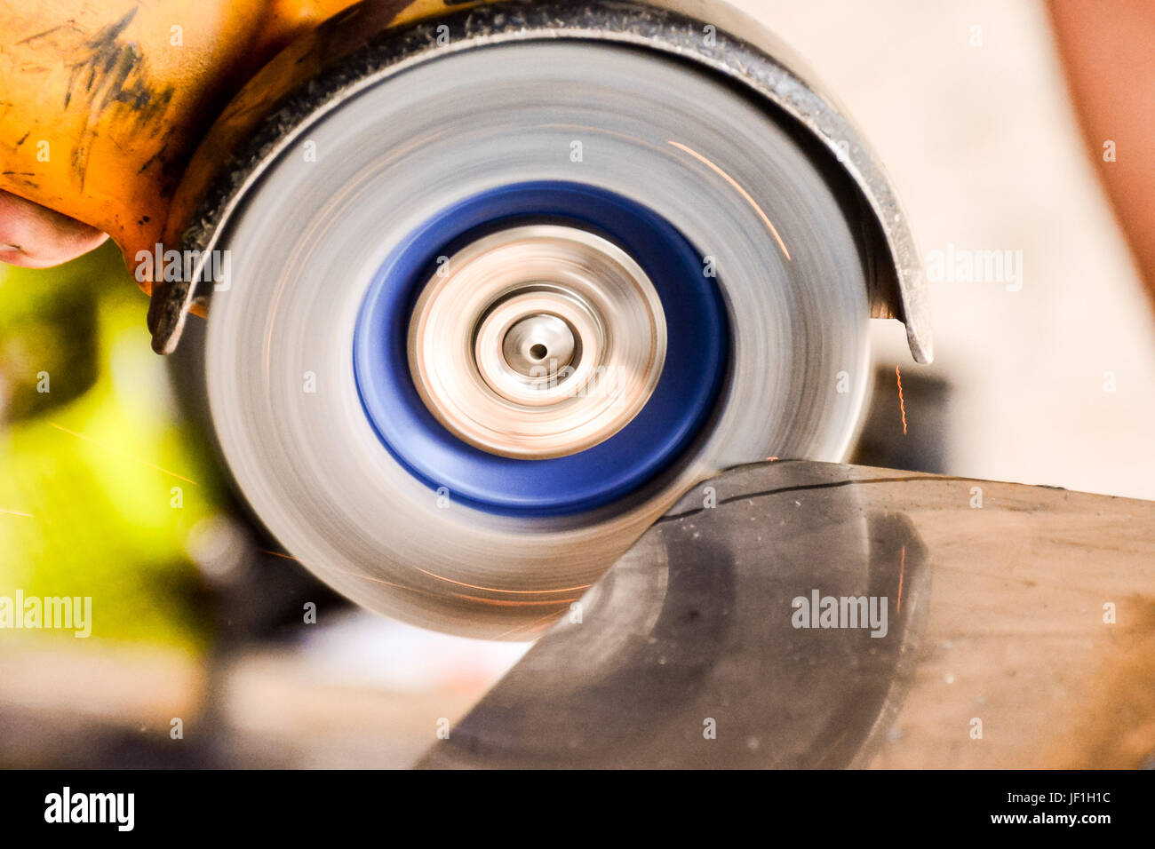 Cutting steel with angle grinder at car service - Stock Image