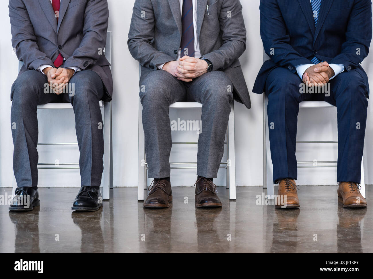 businessmen in suits sitting on chairs at white waiting room. business meeting - Stock Image