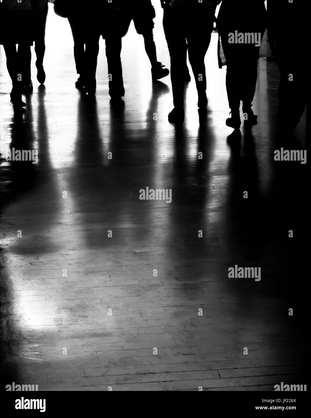Group of people silhouettes and shadows walking in the dark city passage in black and white - Stock Image