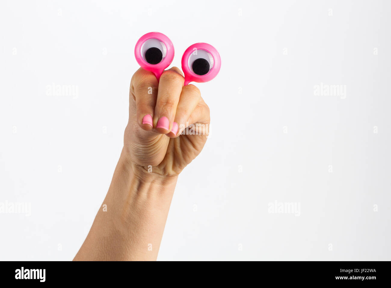 Funny character creature looking contemplating and thoughtful depicted with female hand and googly eyes. Isolated - Stock Image