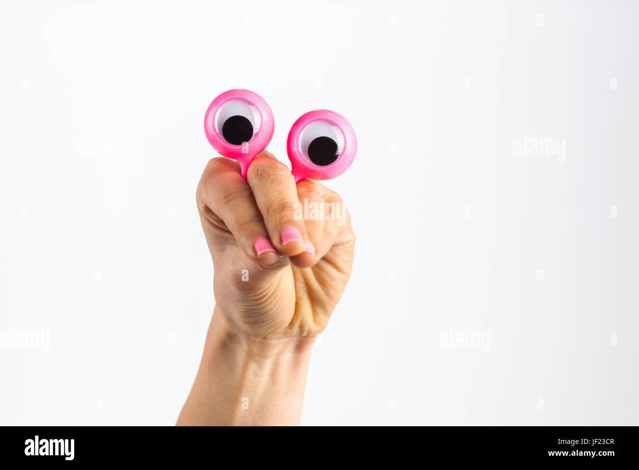 Funny character creature looking very surprised and scared, depicted with female hand and googly eyes. Isolated - Stock Image