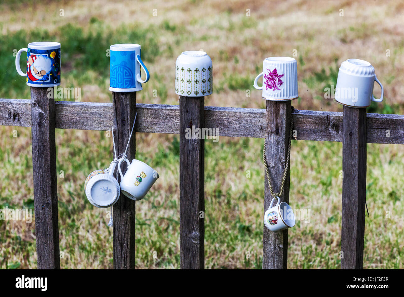 Ceramic cups hanging on the wooden fence, Drying rack, Czech Republic - Stock Image