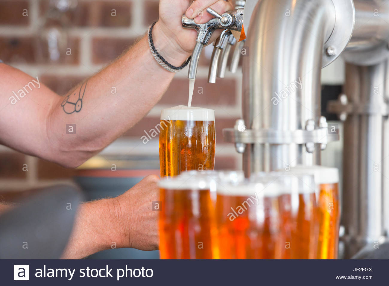 Close Up Of Bartender Pouring Pint Of Beer Behind Counter - Stock Image