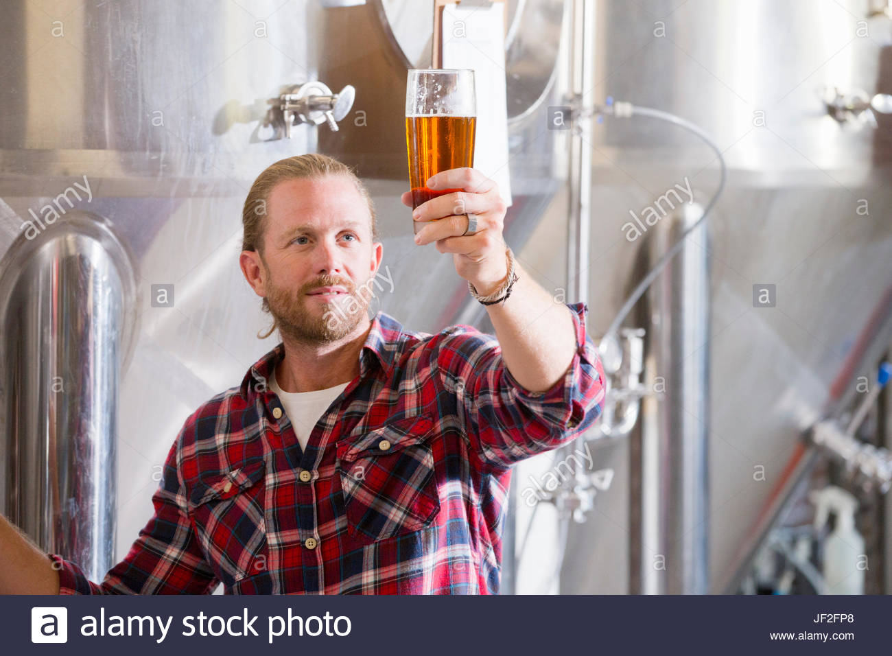 Male Brewery Worker Quality Checking Beer Sample - Stock Image