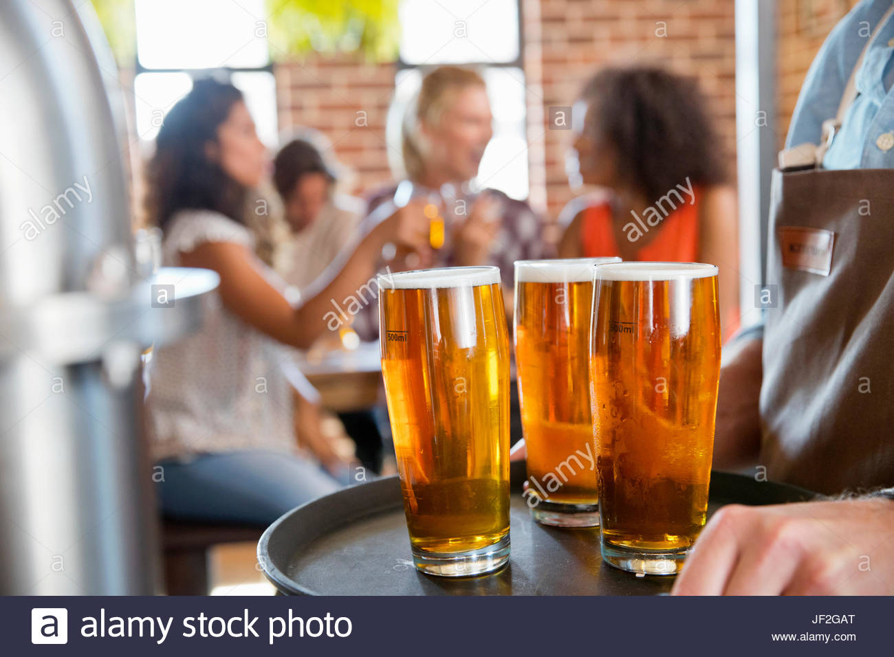 Close Up Of Pints Of Beer With Customers Drinking In Background - Stock Image