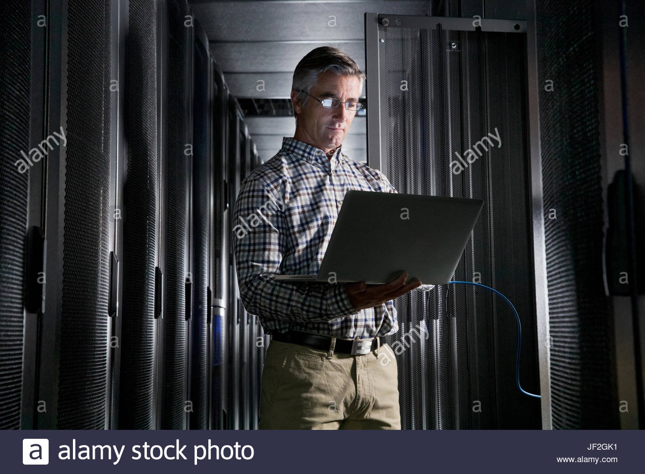 Service Technician With Laptop Working In Secure Data Centre - Stock Image