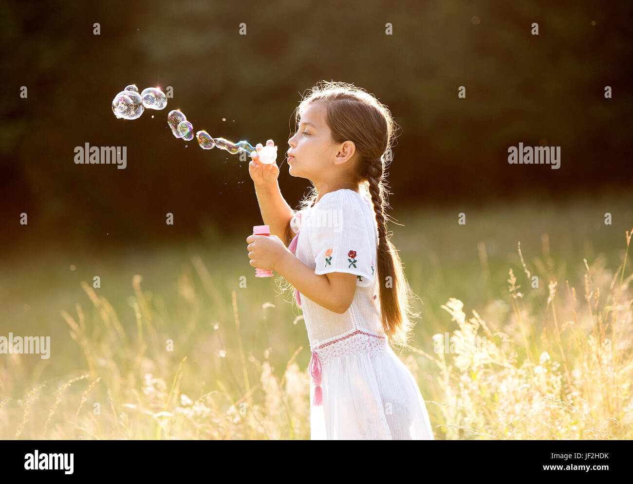 little happy girl with tight braids wearing traditional romanian blouse running outside - Stock Image