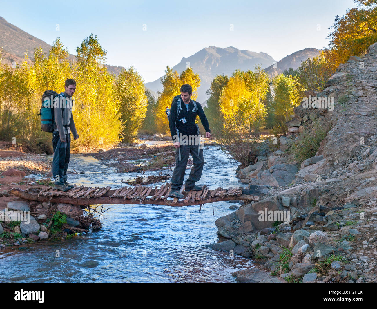 2 young men trekking in the M'Goun region of the Moroccan Atlas crossing a stream on a small wooden bridge - Stock Image