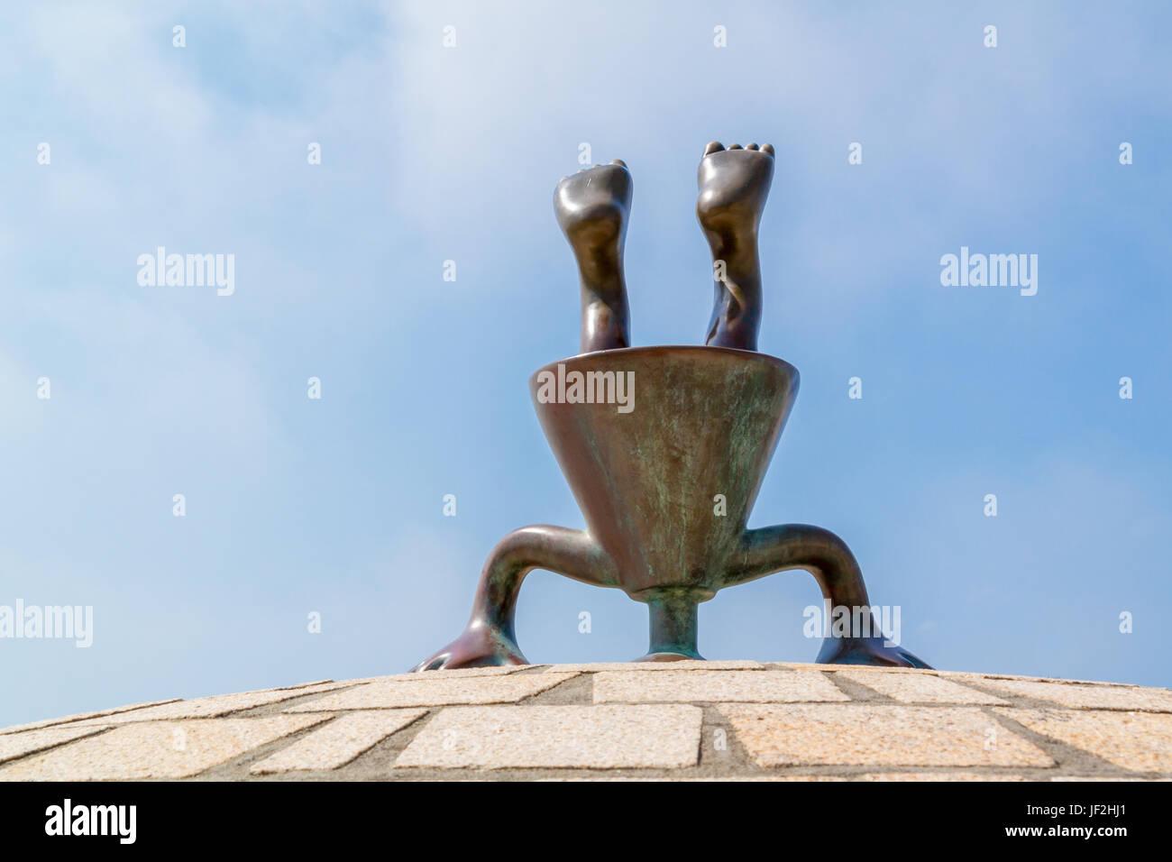 Bronze upside down figure, part of fairytale sculptures by the sea on boulevard of Scheveningen, The Hague, South - Stock Image