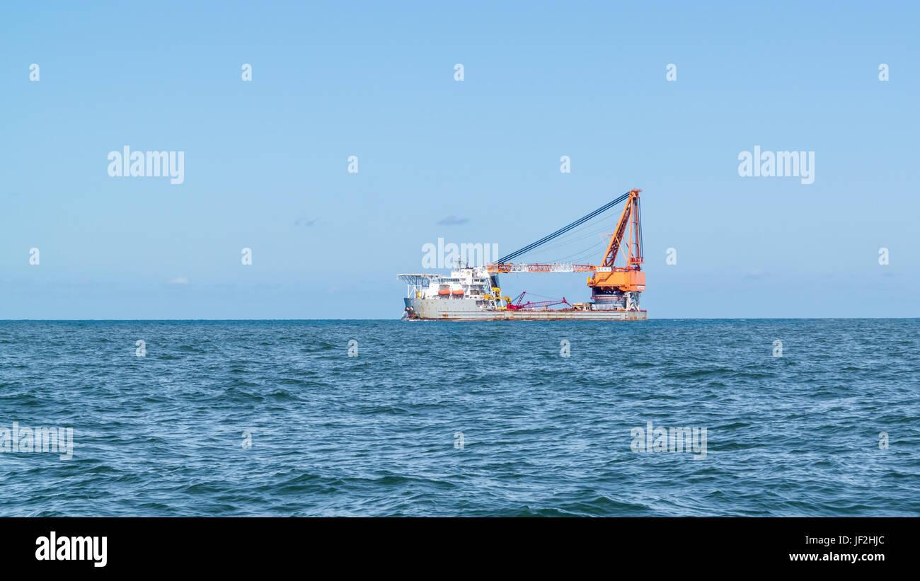 Heavy lift ship with big ship crane sailing on North Sea leaving port of Rotterdam, Netherlands - Stock Image