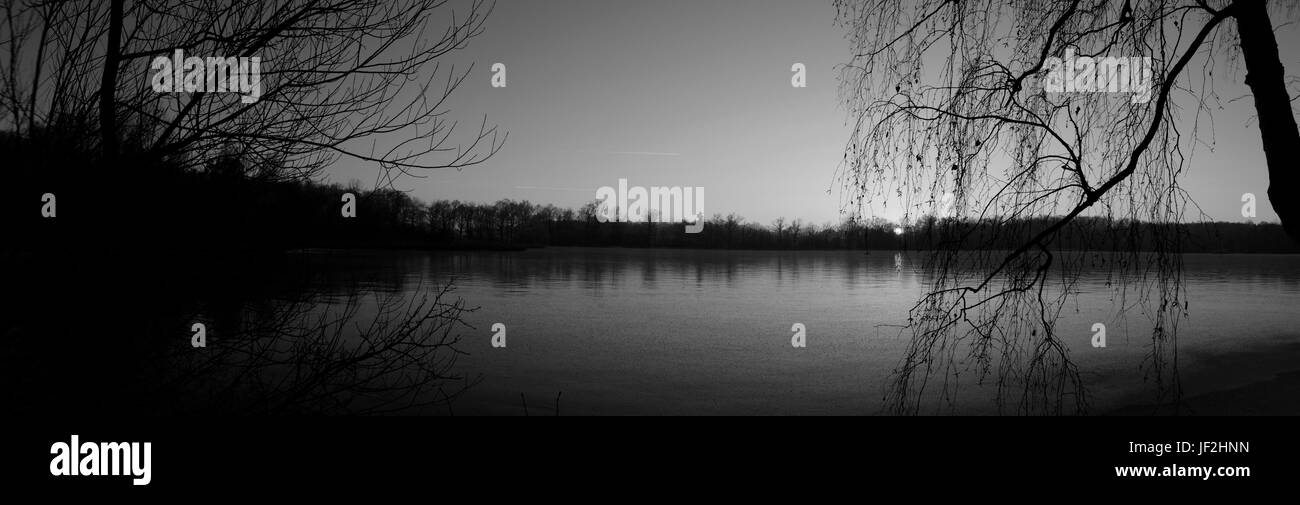 Mirror of darkness on lake in black and white panorama - Stock Image