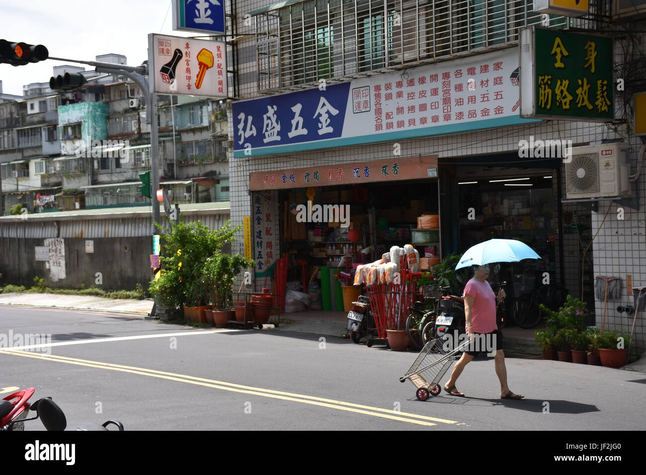 Old woman pulling basket behind her in road near store in New Taipei City. Hot summer day. - Stock Image