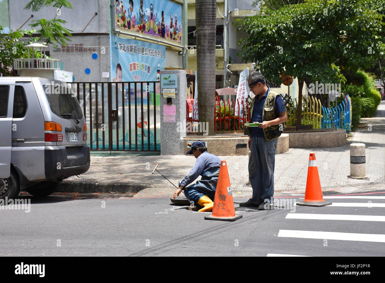 A construction crew man exits a man hole from the sewers below after an inspection of the wiring underground, Taiwan. - Stock Image