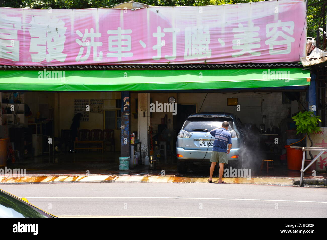 Person washes of mini van during hot summers day in New Taipei City, Taiwan working in their own business. Stock Photo