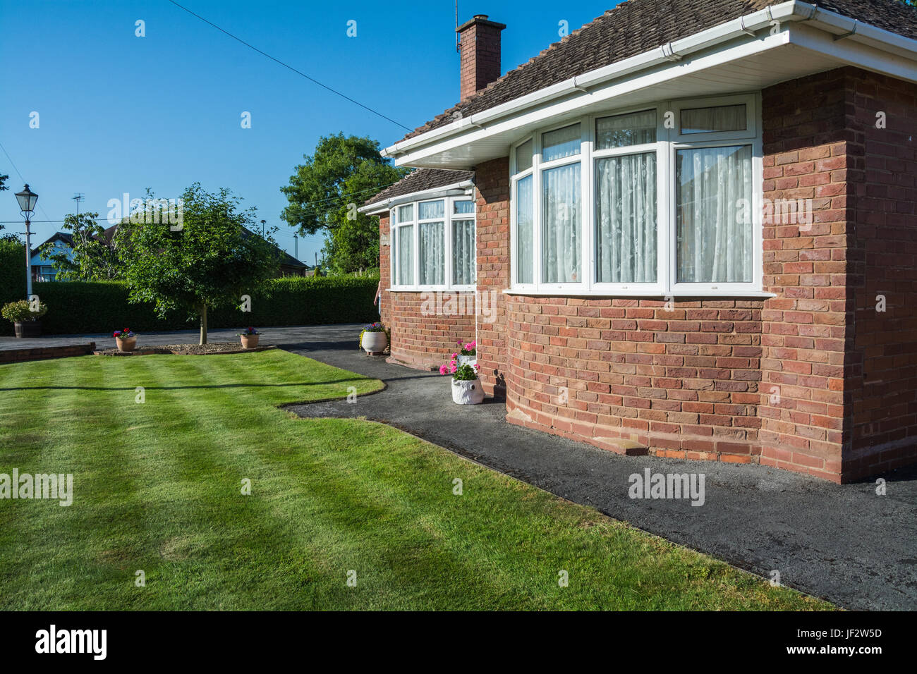 A red brick bungalow with bay windows on a bright sunny day. Shropshire, UK - Stock Image