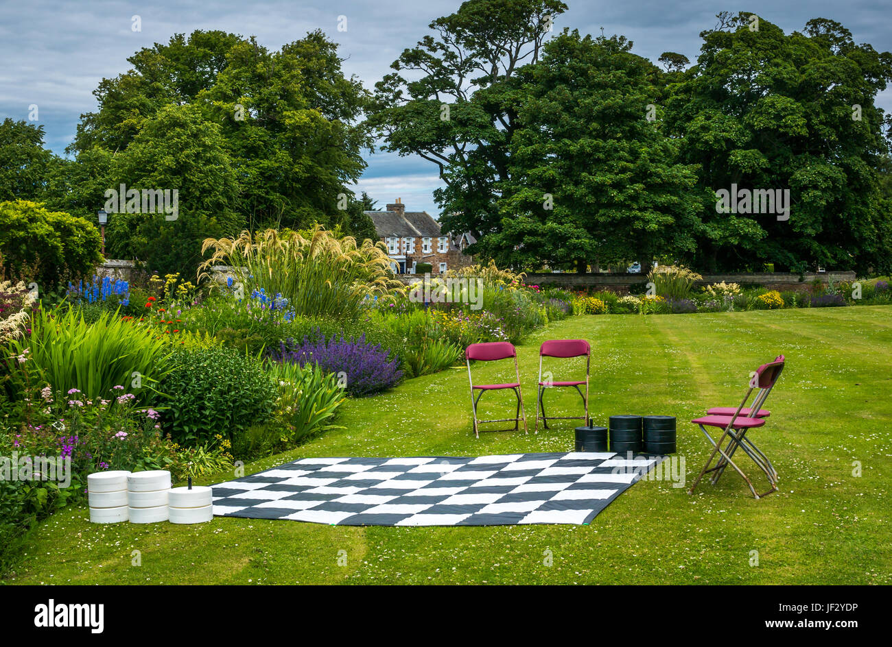 Outdoor giant draughts or checkers game in formal flower garden, Dirleton Castle, East Lothian, Scotland, UK, with - Stock Image