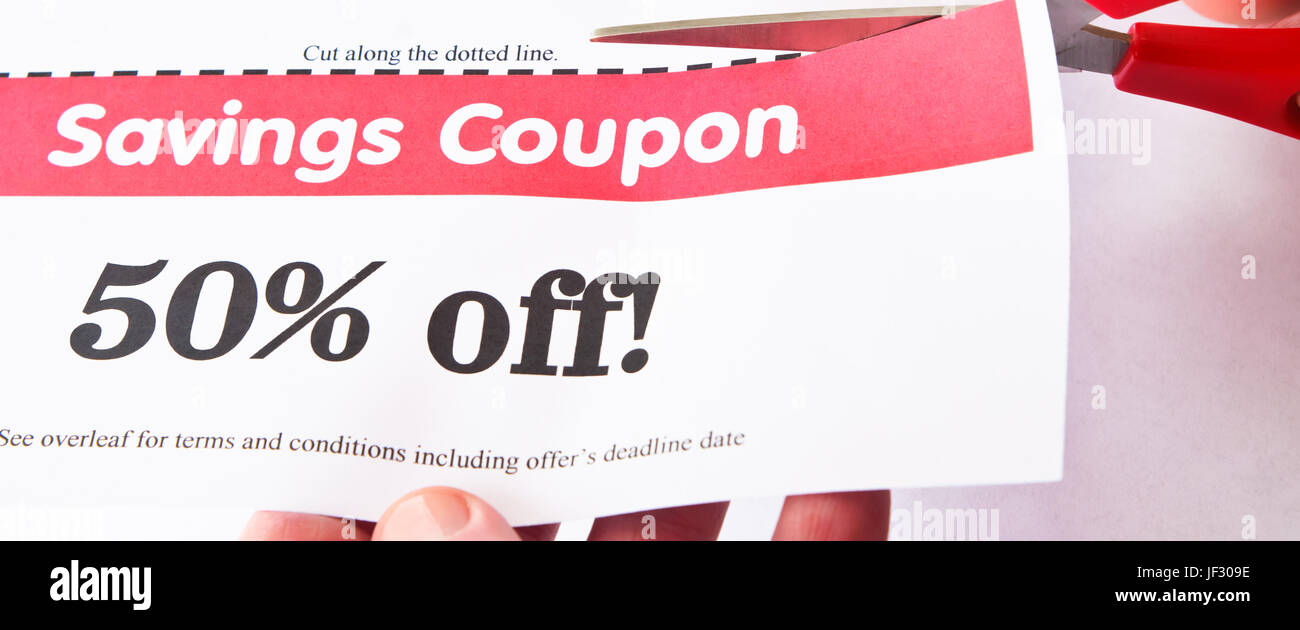 Scissors cutting dotted line of a 50% off savings coupon.  Hands visible. - Stock Image