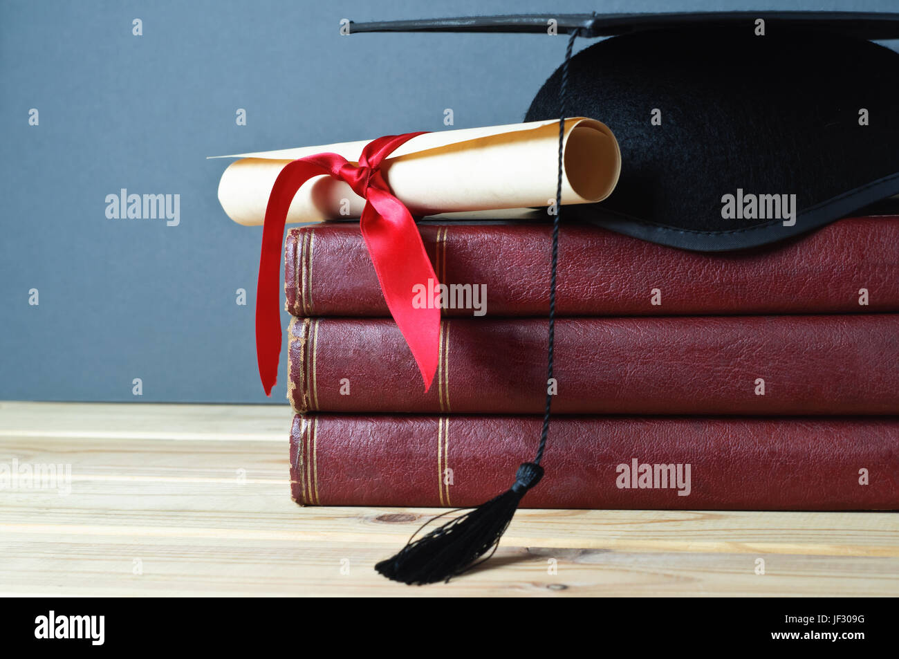 Graduation mortarboard and scroll tied with red ribbon on top of a stack of old, worn books on a light wood table. - Stock Image