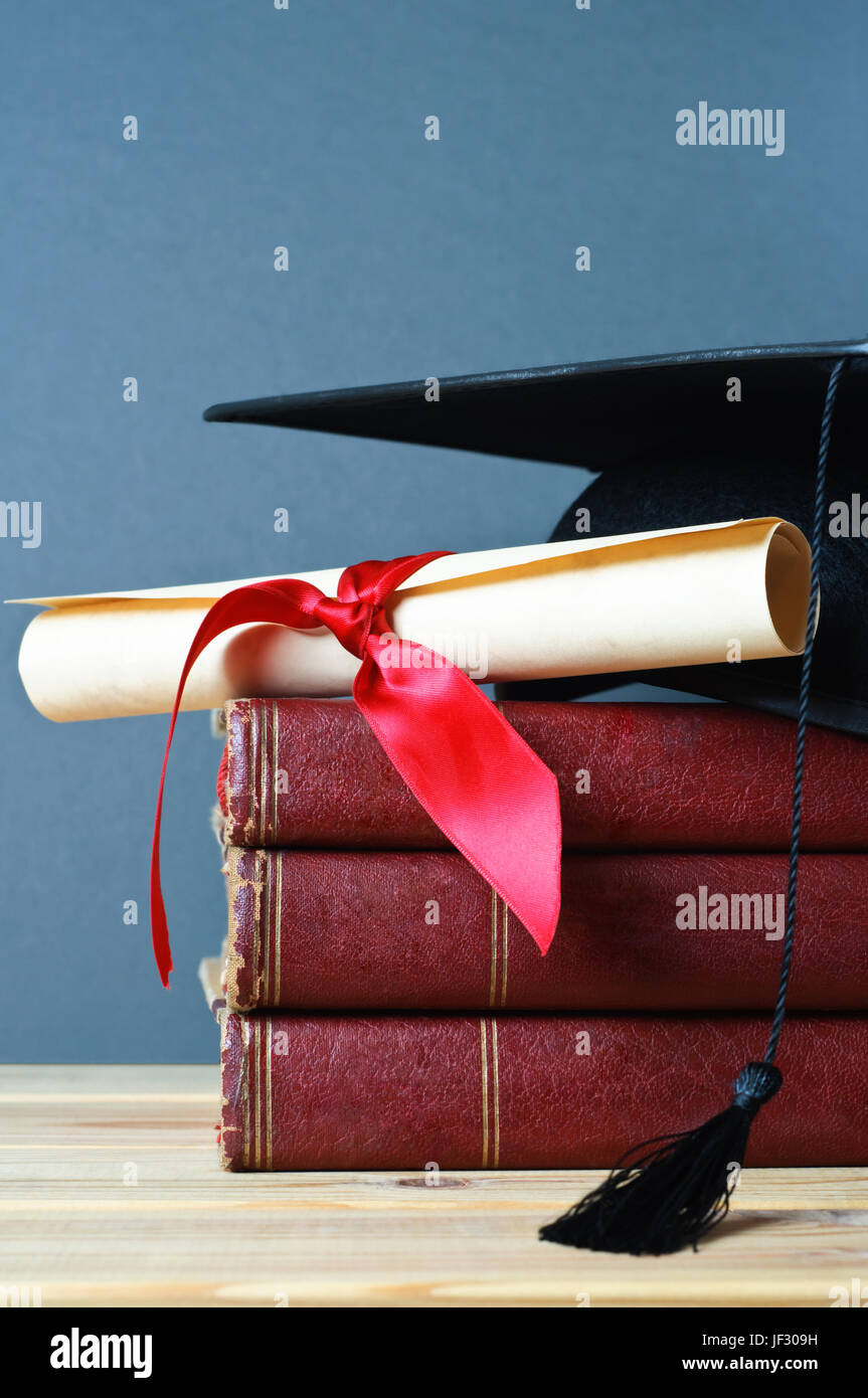 A stack of old, worn books with a mortarboard and ribbon tied scroll on top, placed on a wooden table with a grey - Stock Image
