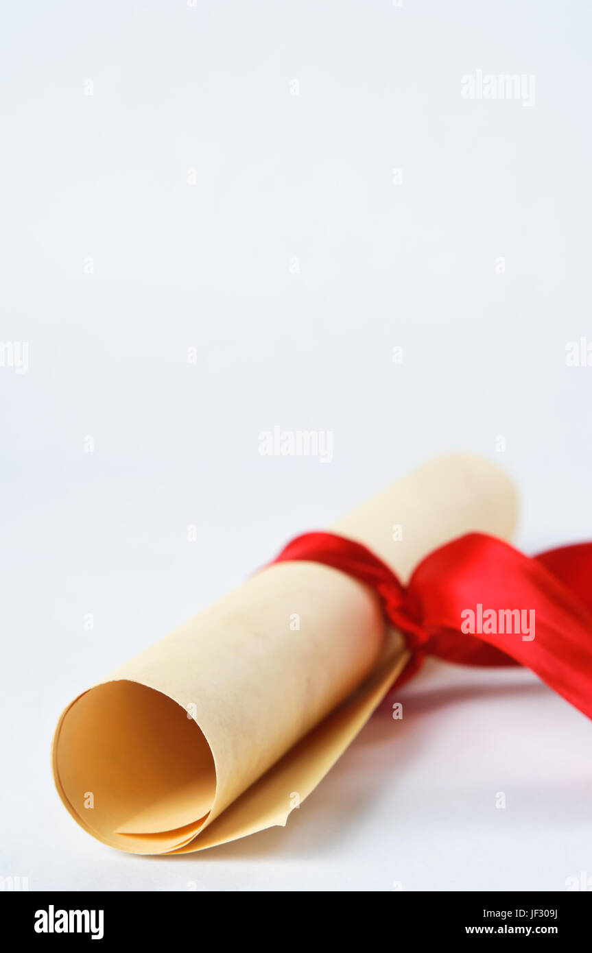 A rolled up parchment scroll, tied with a red ribbon to suggest graduation diploma or award. - Stock Image