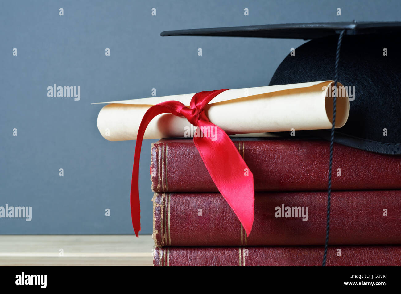 Close up of a mortarboard and graduation scroll on top of a pile of old, worn books, placed on a light wood table - Stock Image