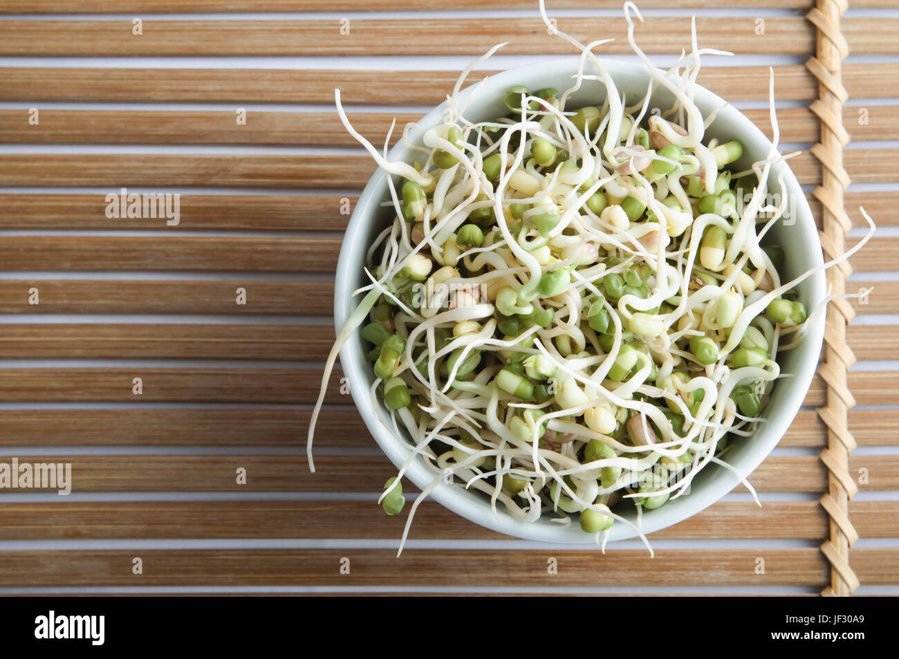 Overhead shot of a bowl of mung beansprouts, standing on a slatted bamboo mat. - Stock Image