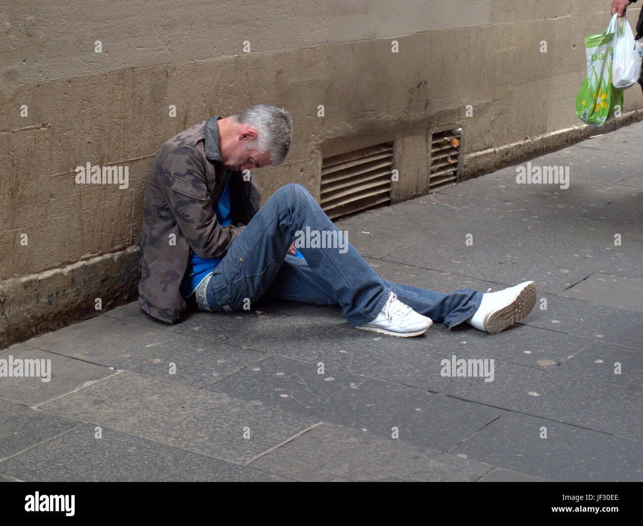 zombie drug spice begging homeless unemployed man lying on the Stock
