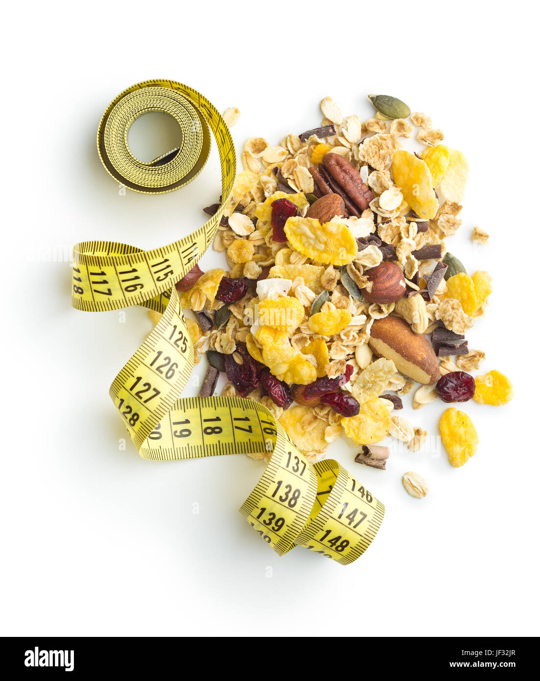 Tasty homemade muesli with nuts and measuring tape isolated on white background. Diet concept. - Stock Image