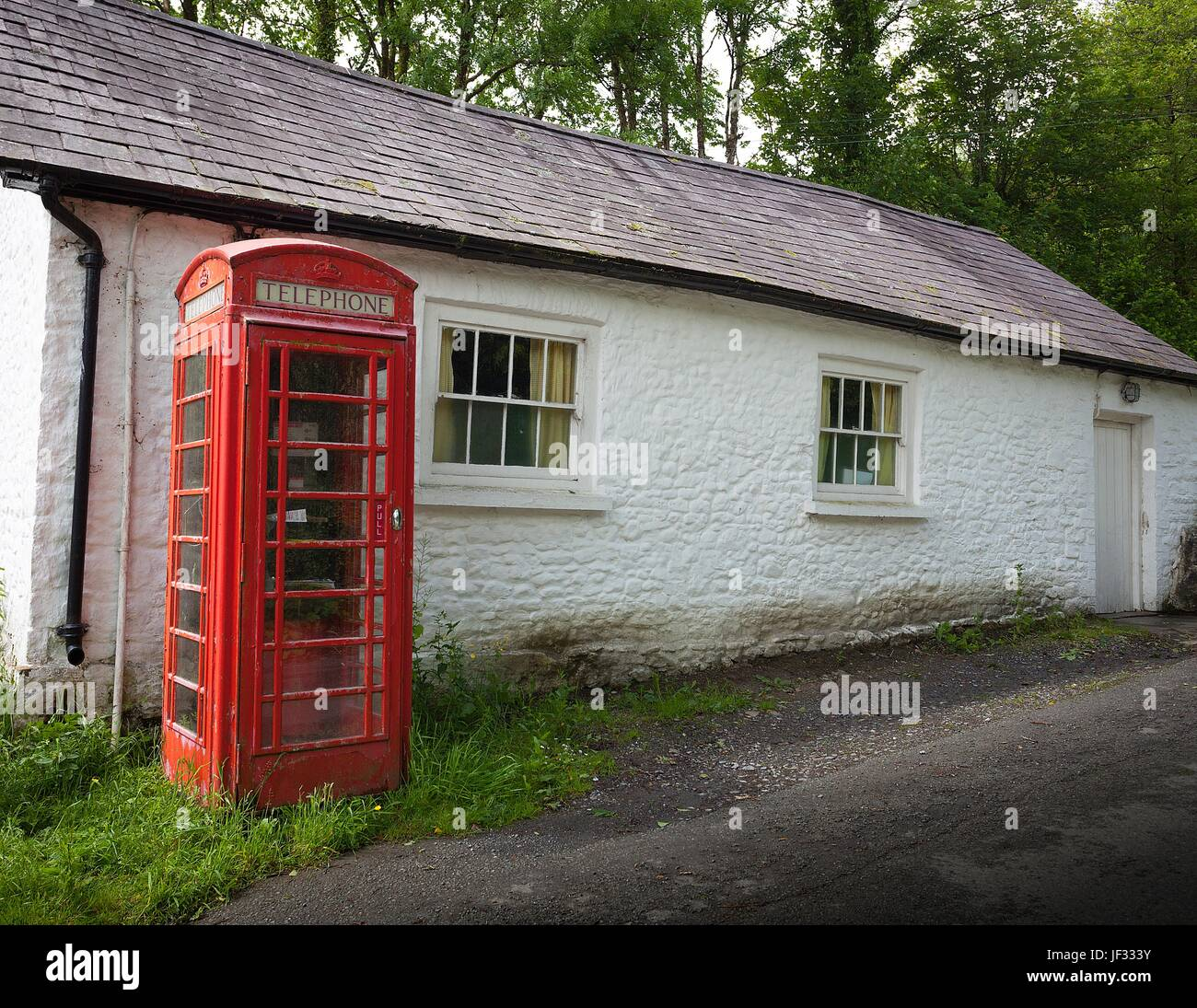 An old British phone box and a white washed building - Stock Image