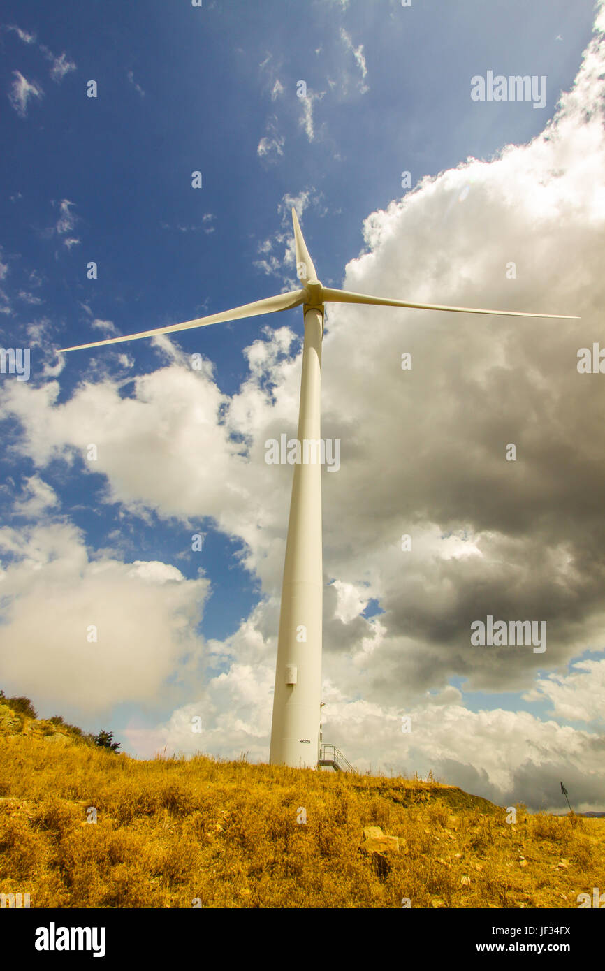 A white three bladed wind turbine against a clouded blue sky. Italy, Sicily - Stock Image